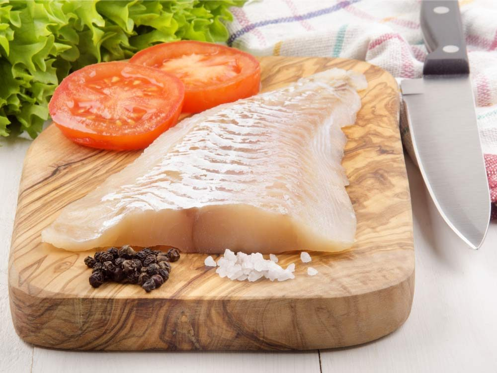 Haddock fillet with pepper and tomato on wooden cutting board