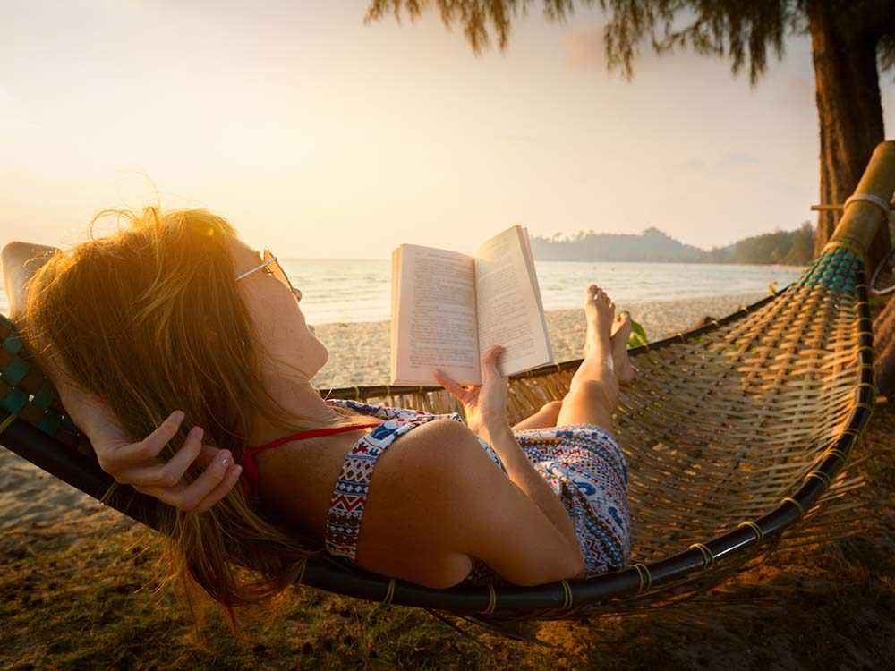 Island getaway with woman reading on beach