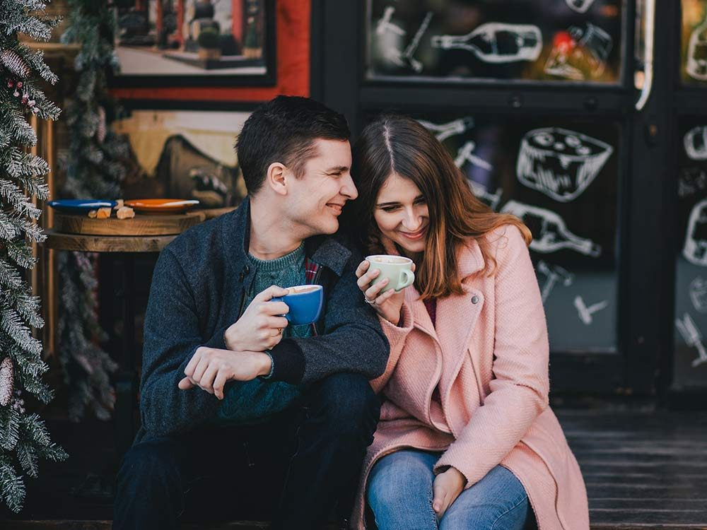 Couple laughing while drinking coffee
