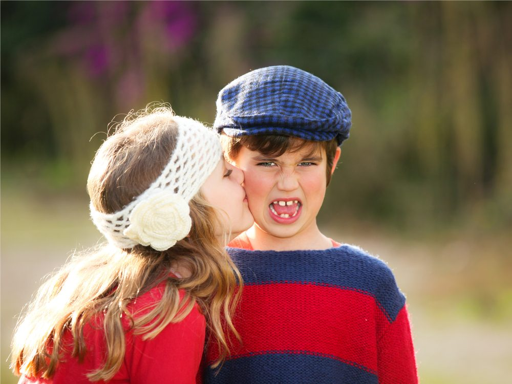 Young little girl kissing embarrassed boy