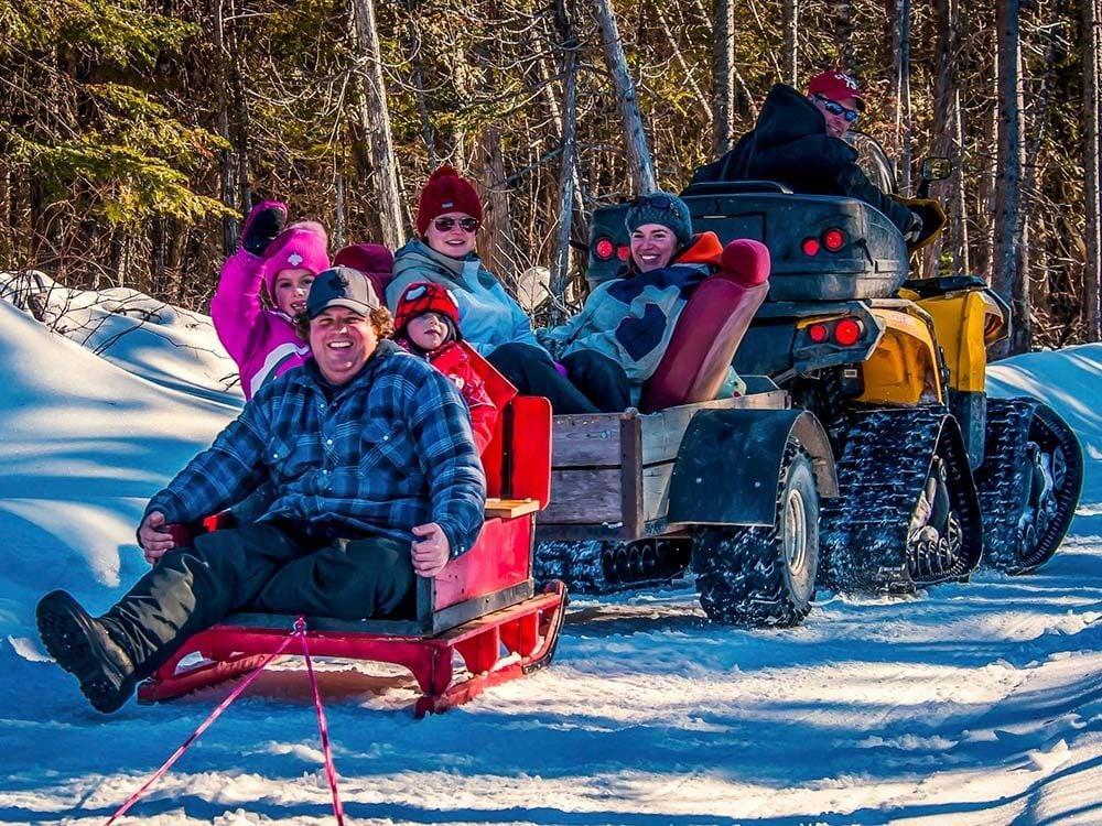 Two families enjoying winter fun in the woods