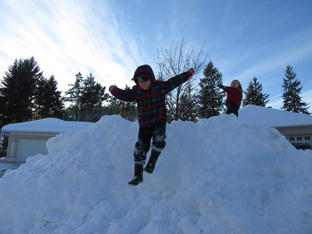 Young brothers playing on snow hill