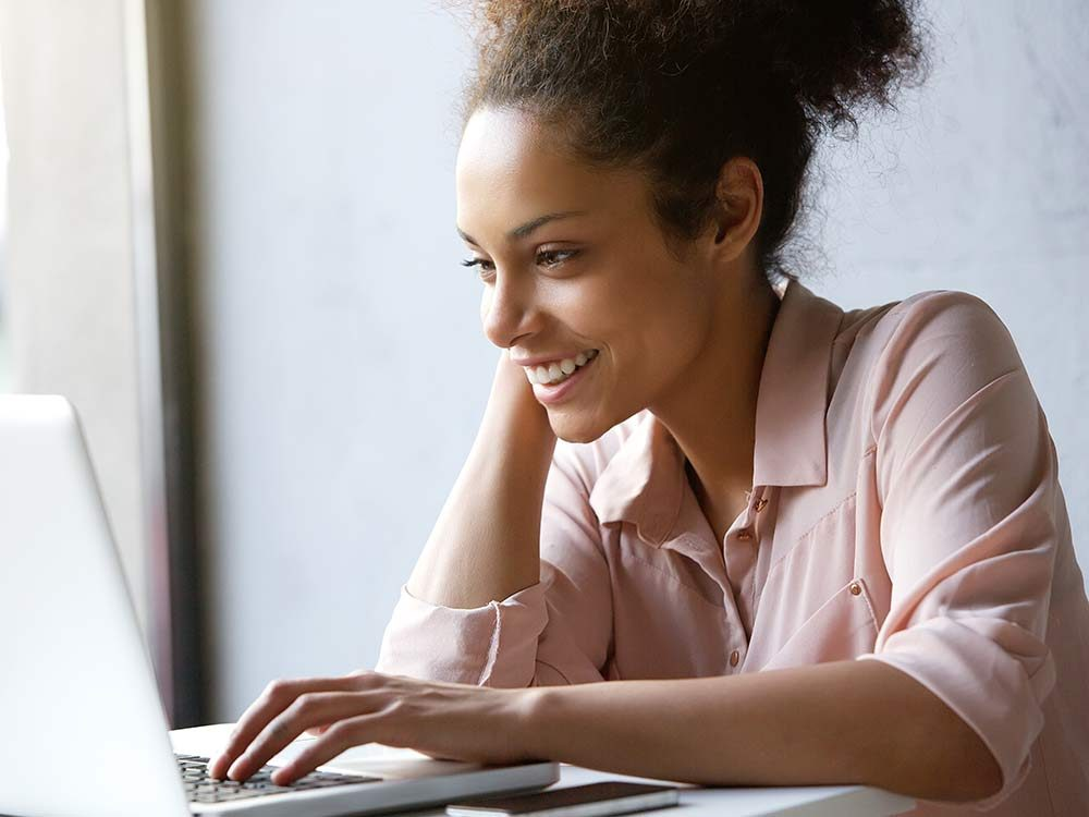 Happy woman researching on laptop