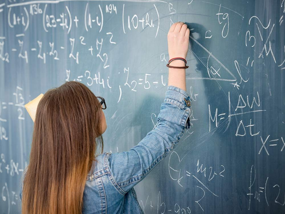 Woman solving math equation on chalkboard