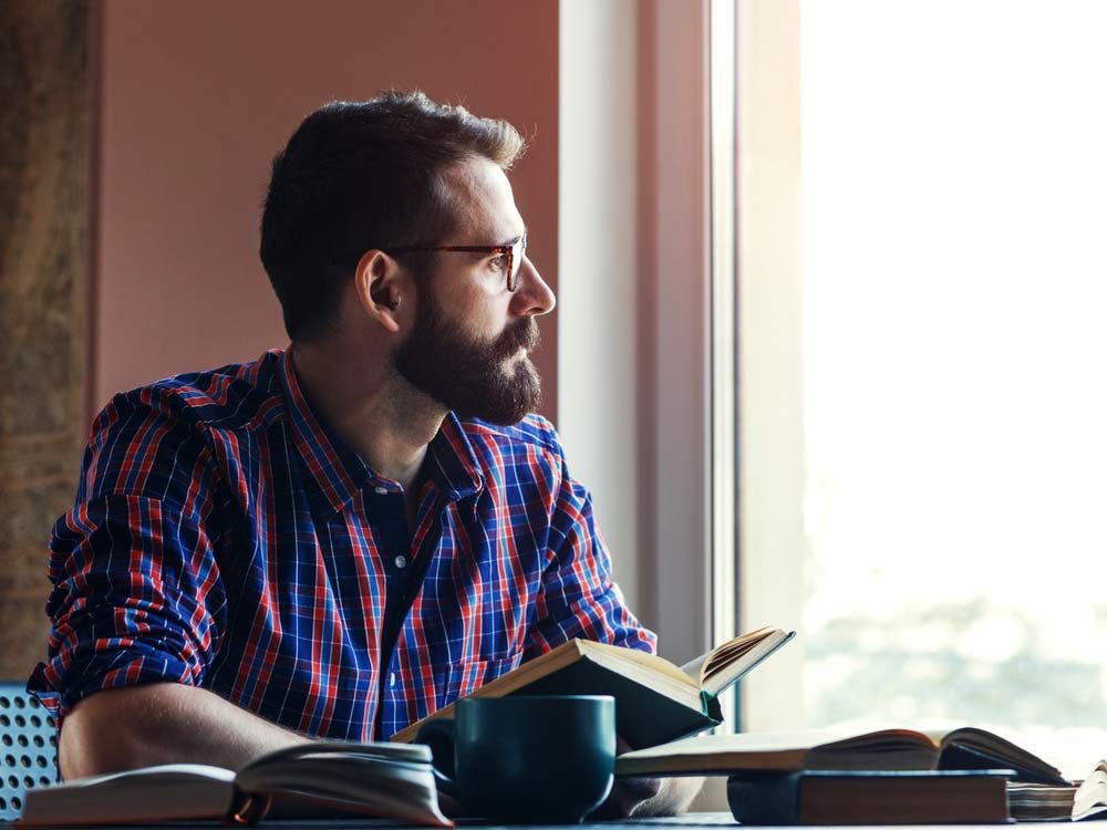 Bearded man reading a book