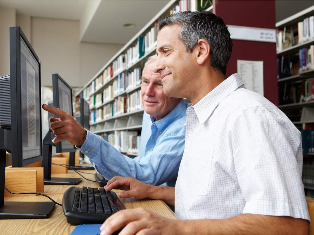 Two older men using computer at public library