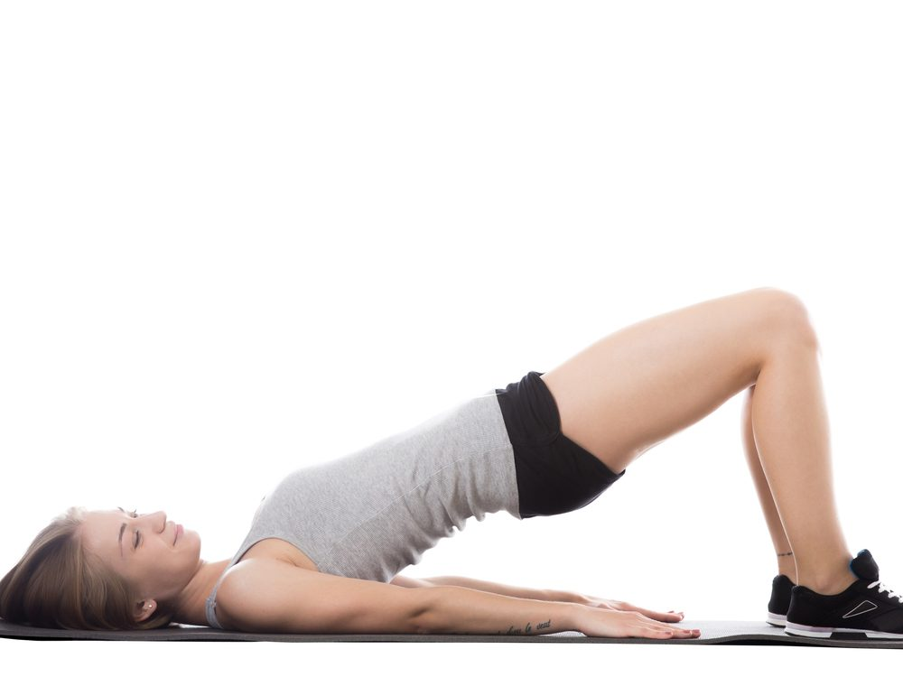 The two-leg floor bridge is a core stability exercise that flattens your abs without crunches
