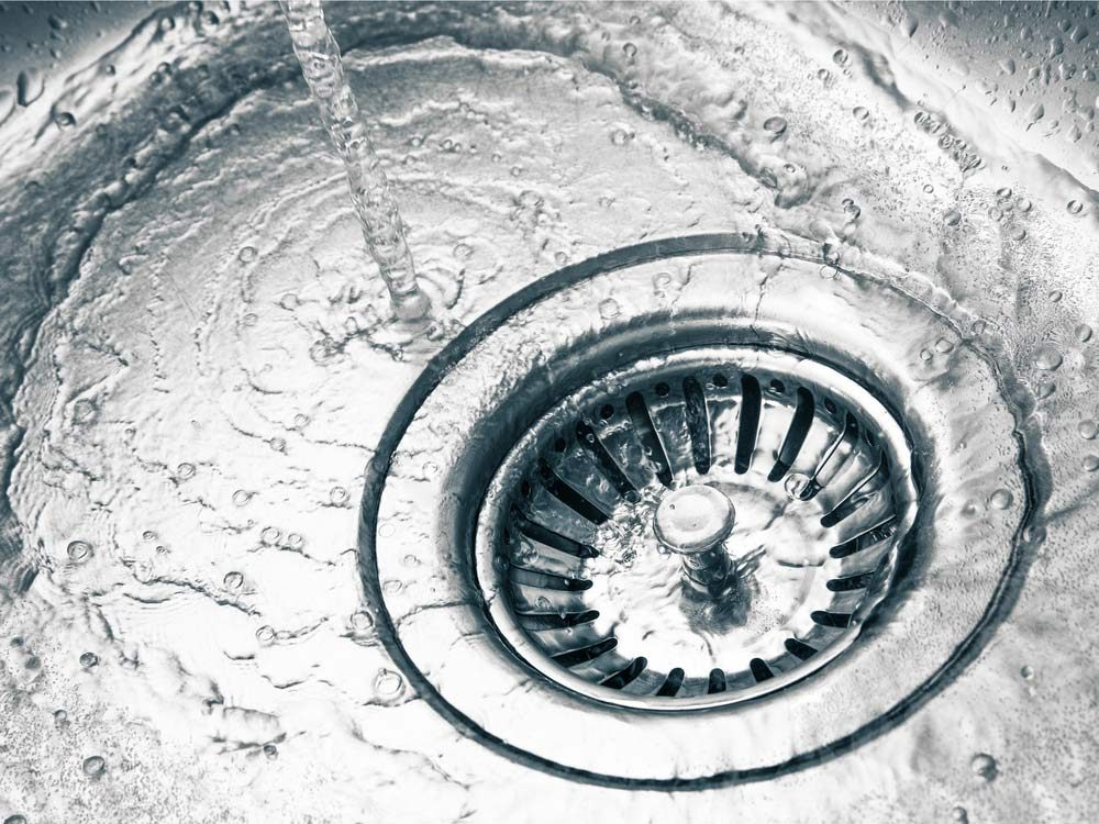 Water pouring down sink drain