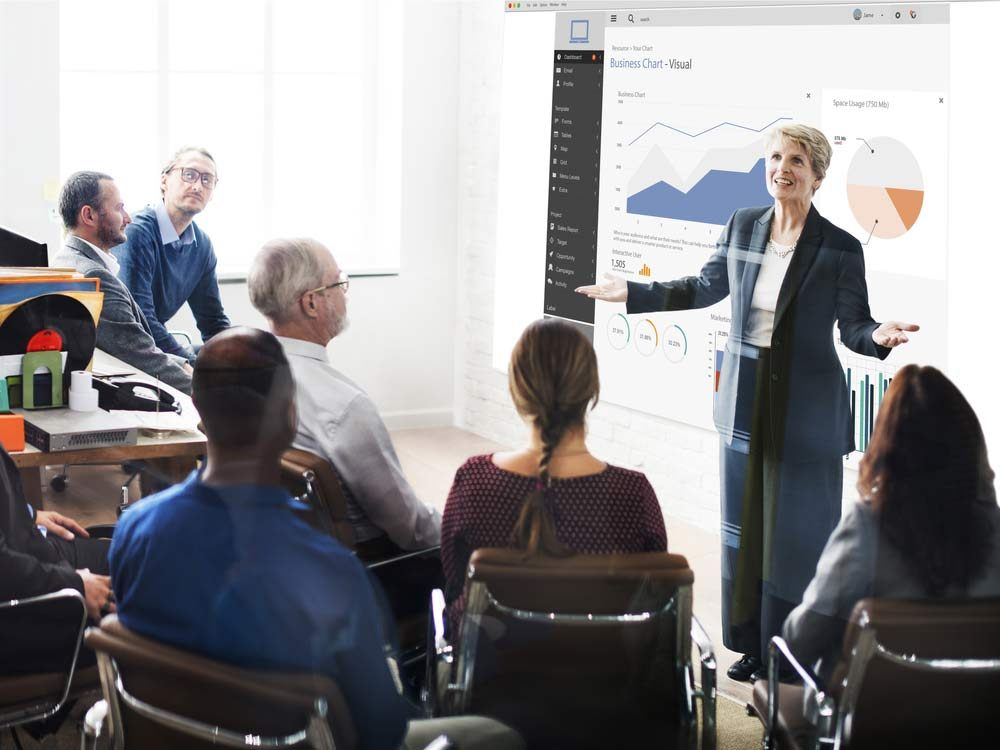 Mature woman giving presentation in office