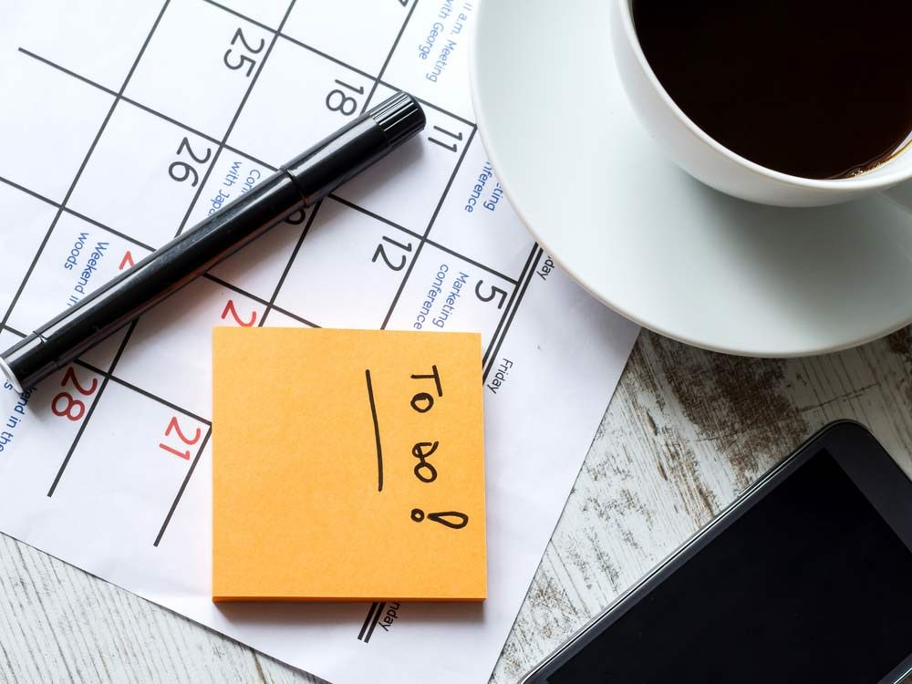 Calendar with sticky note and coffee
