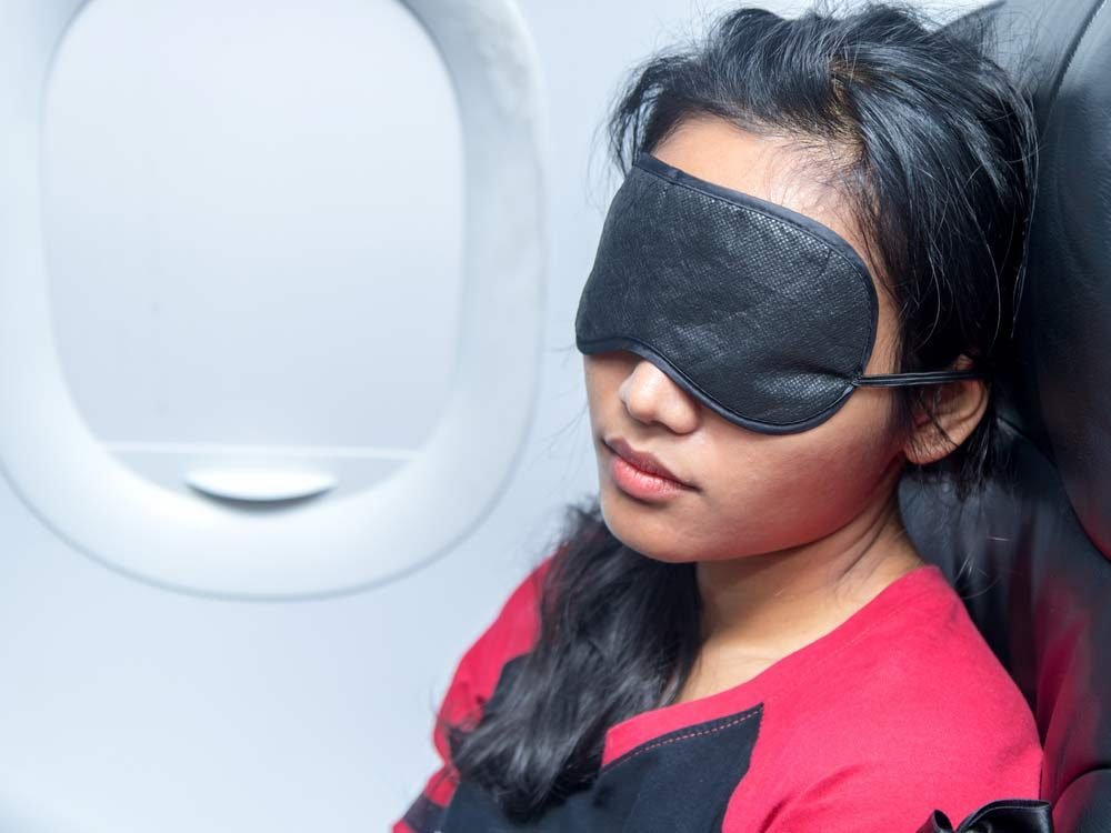 Woman wearing eye mask on flight