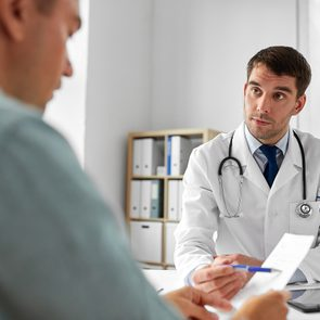 doctor giving prescription to patient at medical office in hospital