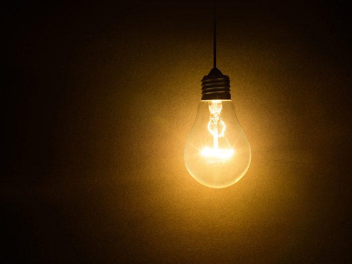 Light bulb jokes - light bulb on dark background, concept of creativity.