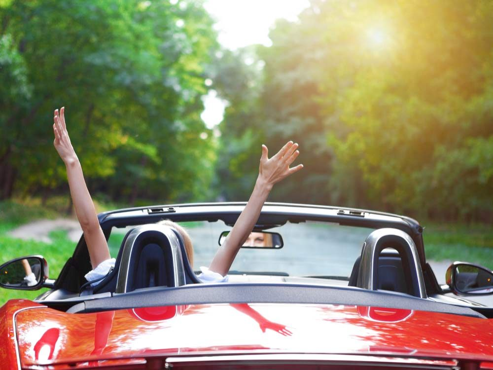 Woman driving red converible