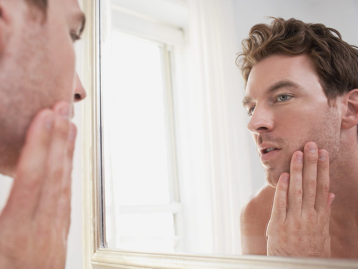 Is mineral sunscreen better - man examining reflection in mirror