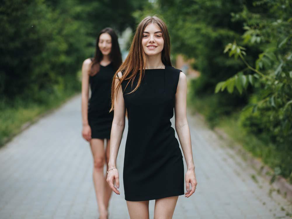 Two women wearing black dresses