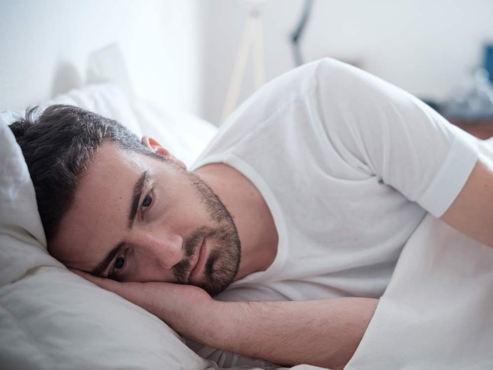 Depressed man laying in bed