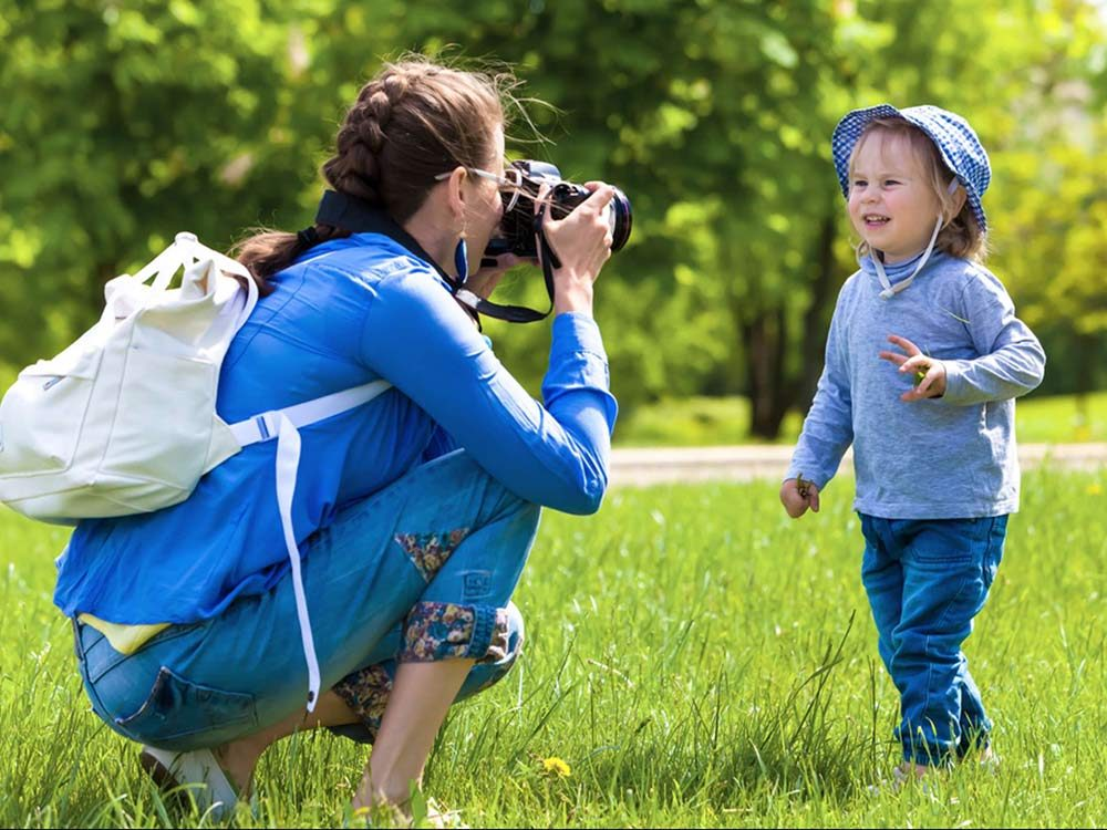 Mother taking photos of child