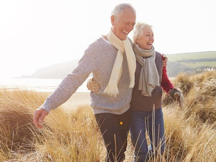 Sex after 50 - senior couple walking on beach