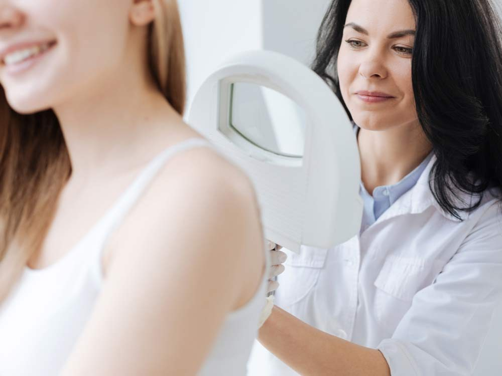 Dermatologist examining skin tags on patient