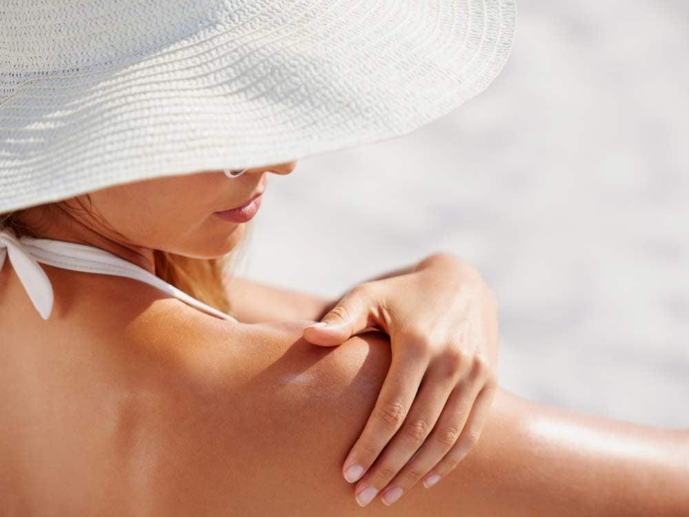 Woman at beach applying sunscreen
