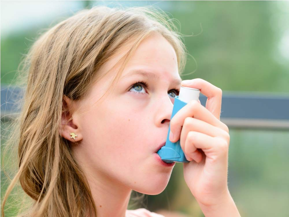 Little girl with asthma using inhaler