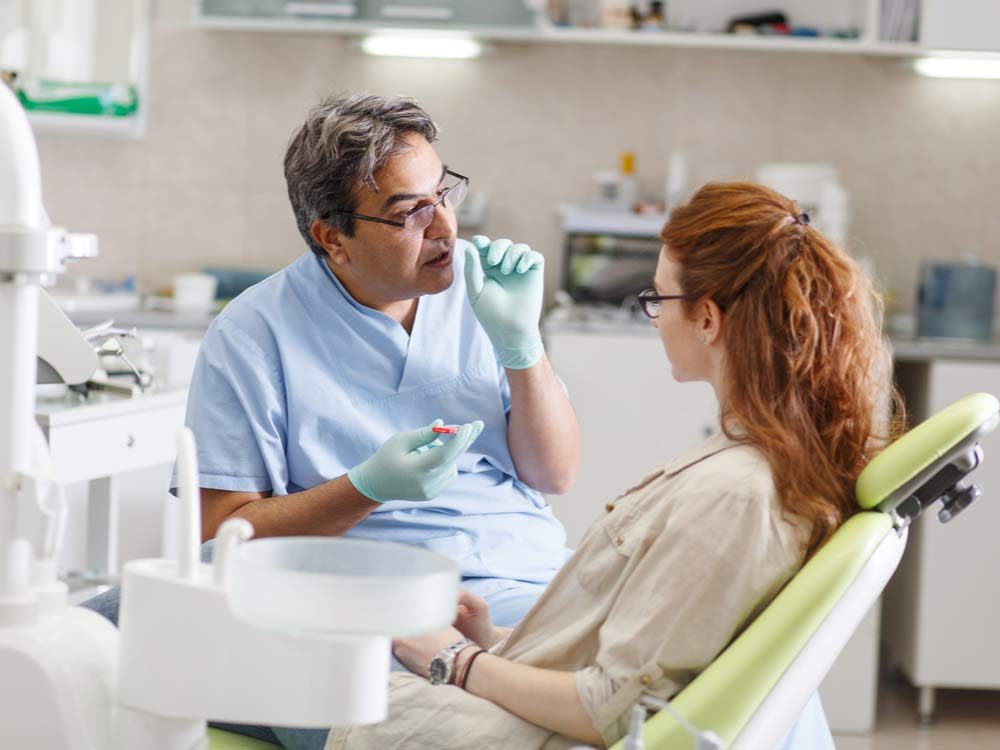 Dentist speaking with female patient