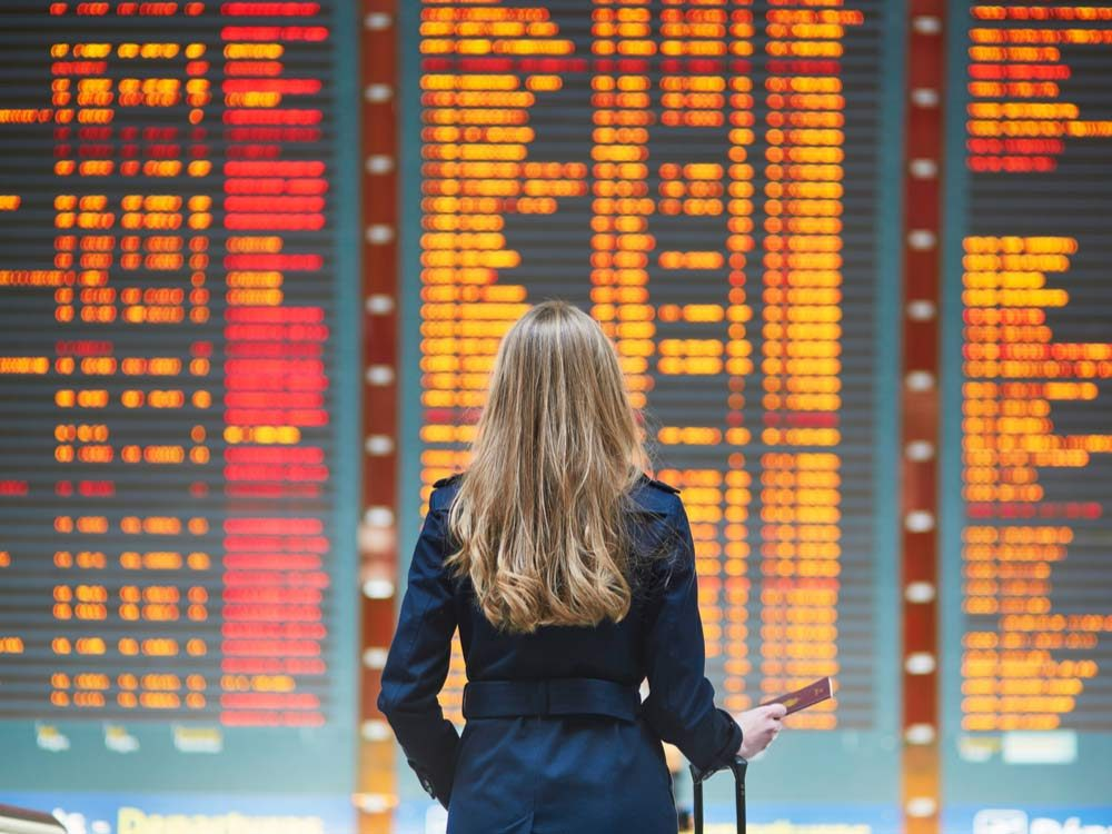 Woman in front of schedule board at airport