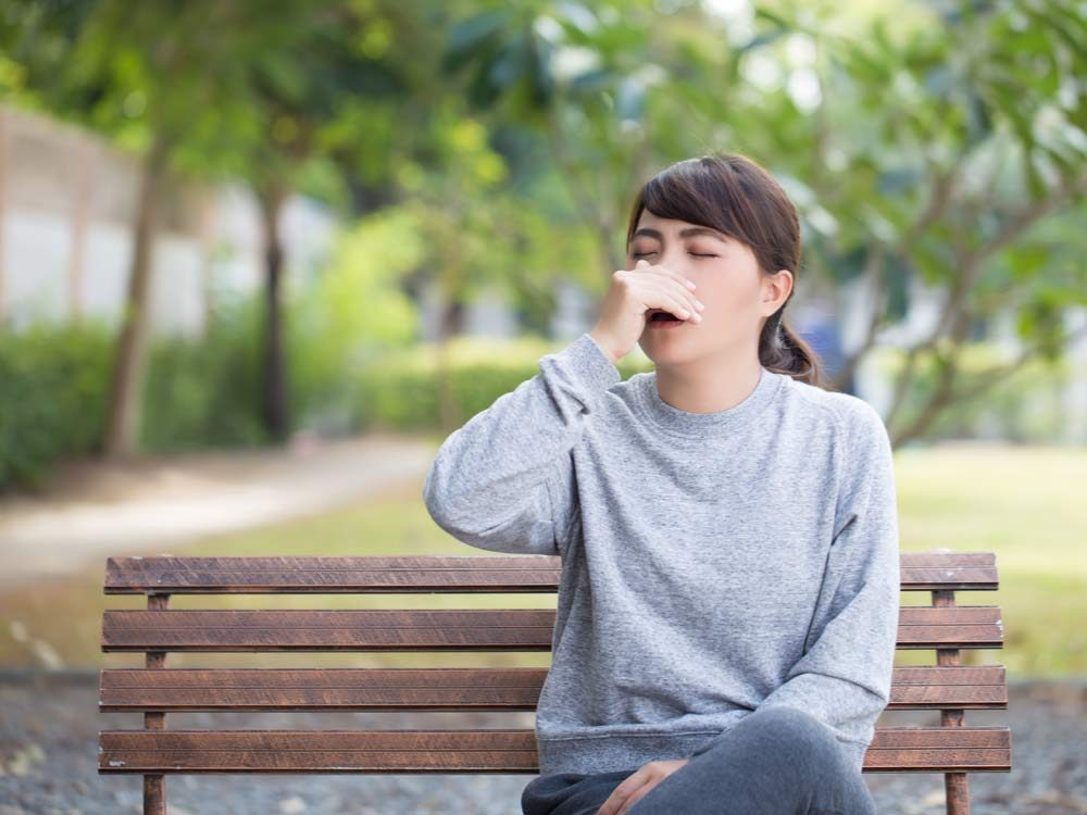 Woman sneezing on park bench