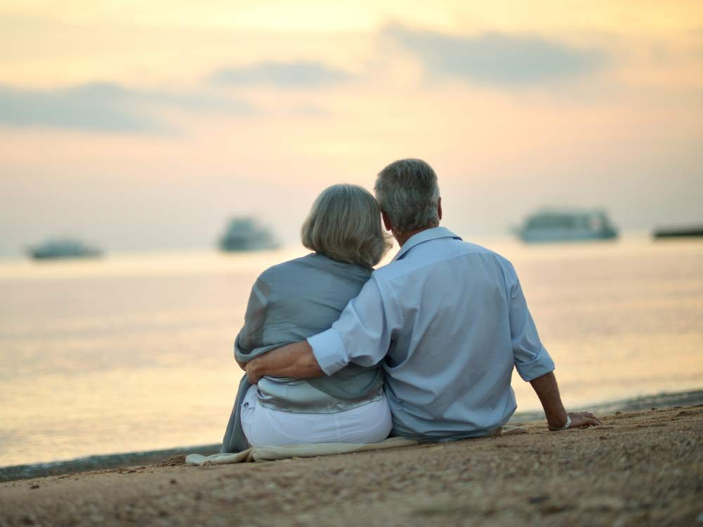 Happy mature couple relaxing on beach watching the sunset