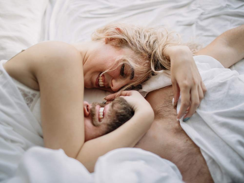 Loving couple luxuriating in bed