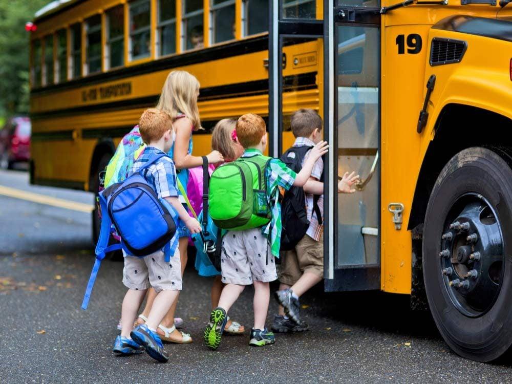 Children boarding yellow school bus