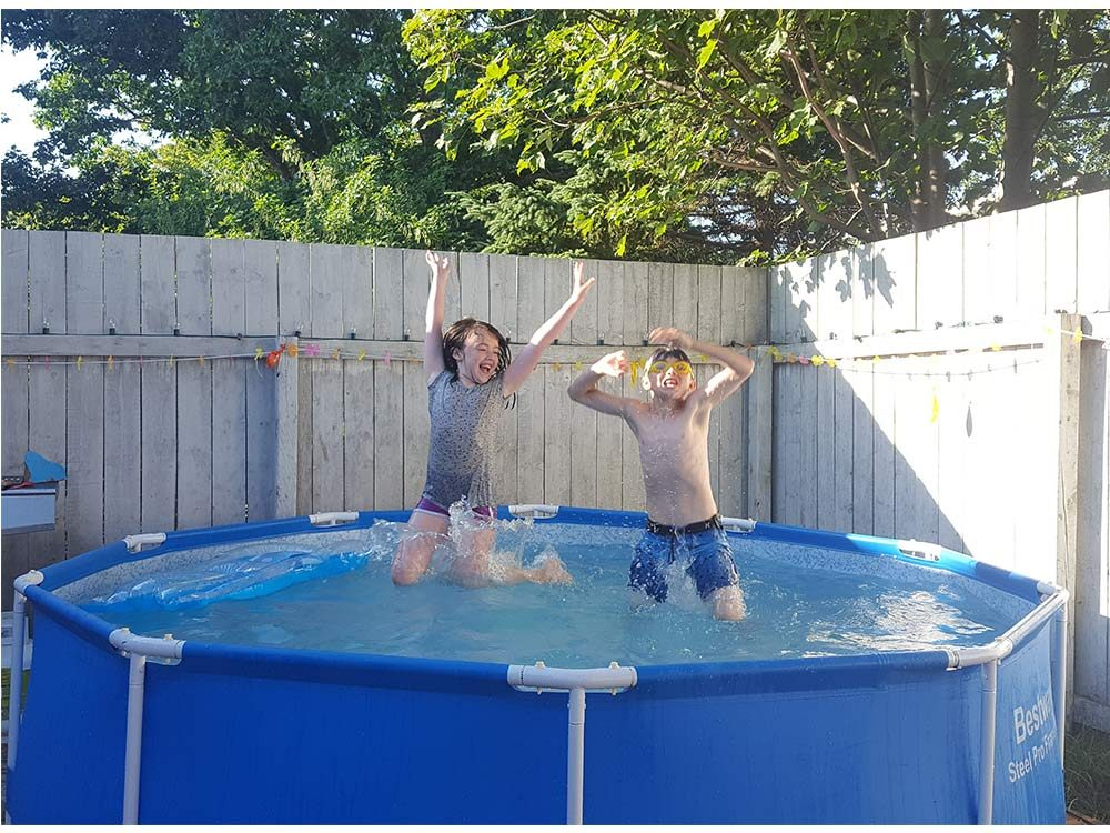 Two children swimming in backyard