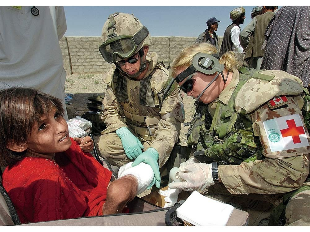 Canadian soldier helping child in Afghanistan