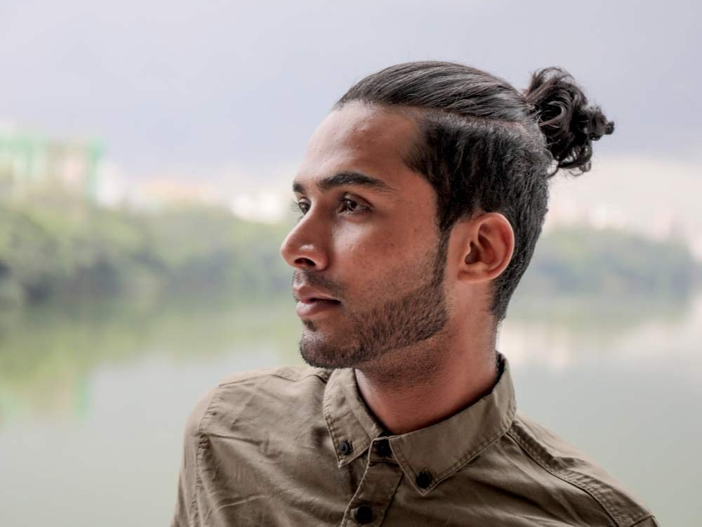 Young man wearing man bun hairstyle
