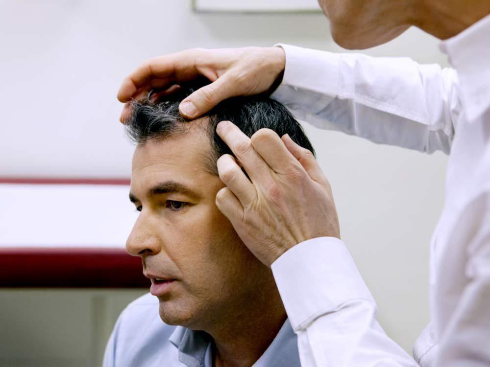 Dermatologist examining patient's hair