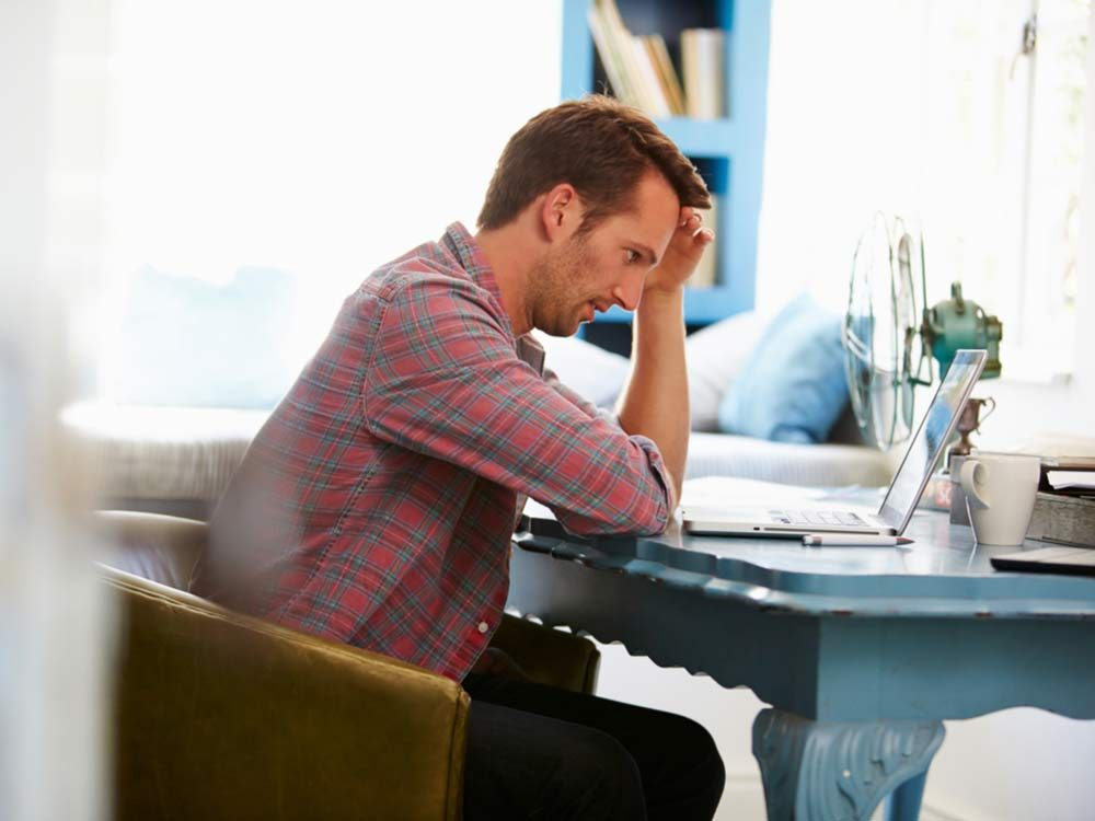Stressed man at desk at home