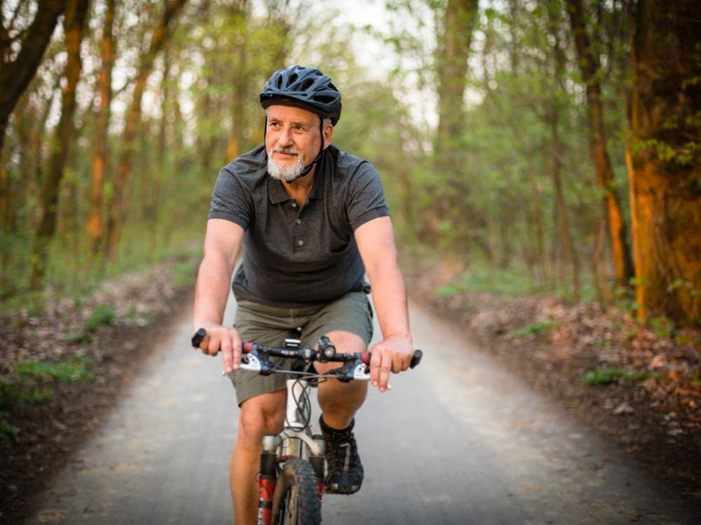 Senior man riding bike in wooded area