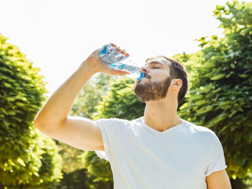 Man drinking water outdoors