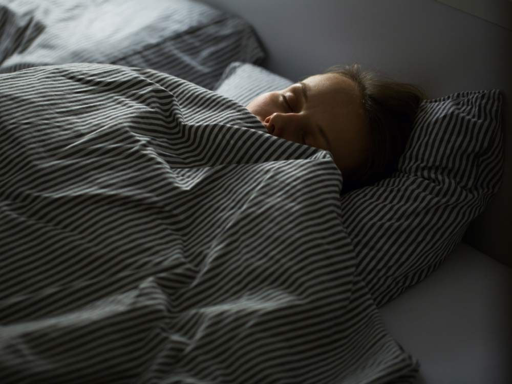 Woman sleeping under comforter