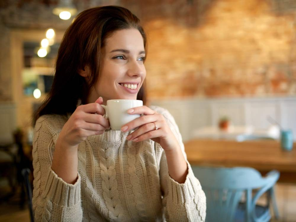 Woman smiling while holding a cup of coffee