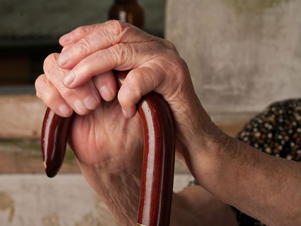 Senior woman's hands clutching cane