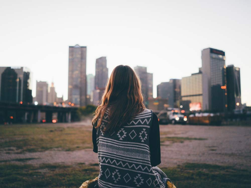 Woman sitting on bench looking at skyline