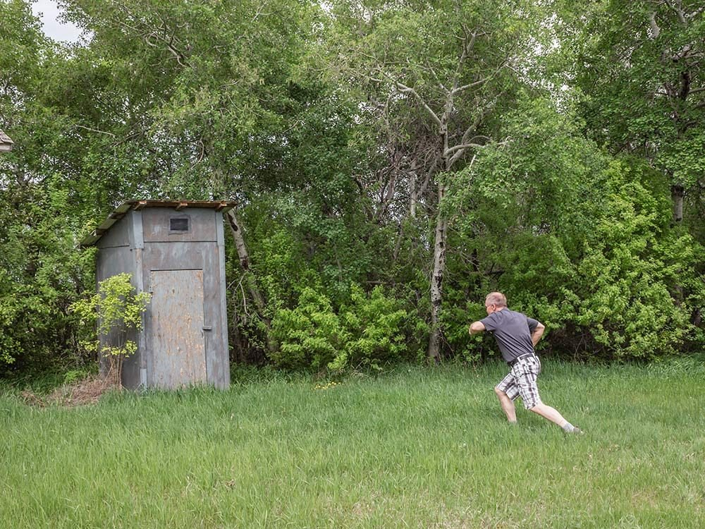 Man running towards outhouse