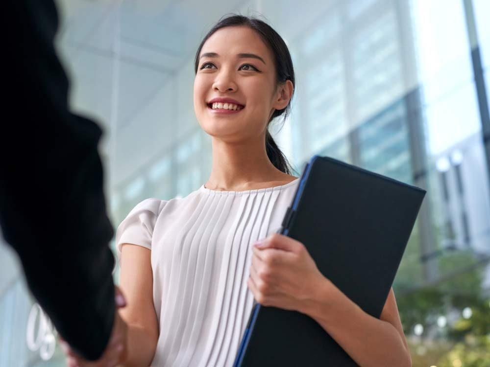 Attractive woman shaking hands with employer