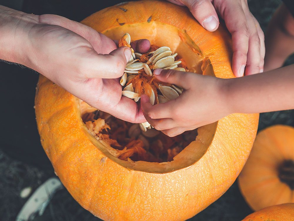Scooping pumpkin seeds from a jack-o'-lantern