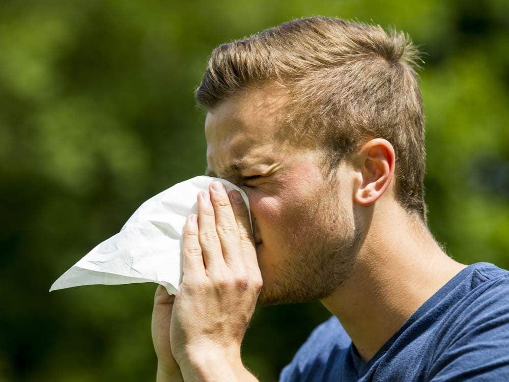 Man blowing his nose into handkerchief