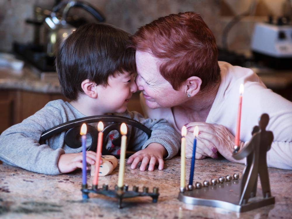 Jewish child and grandmother celebrating Hanukkah