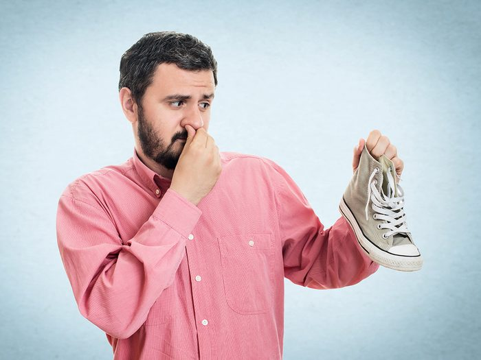 DIY smelly feet solutions - man holding smelly shoe