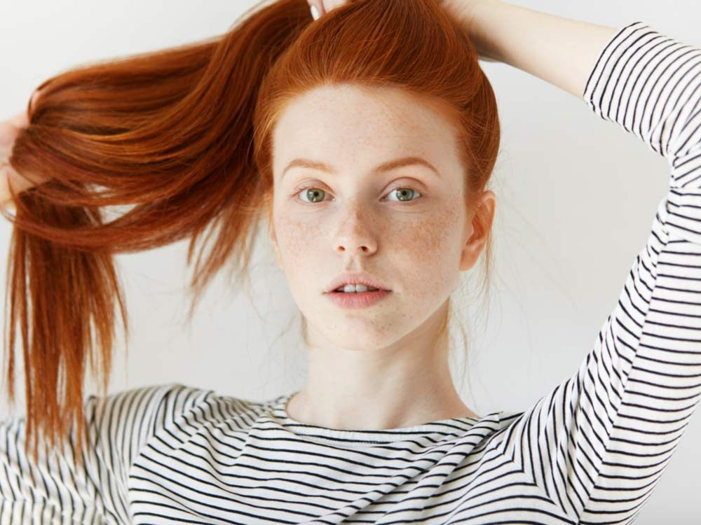 Red haired woman with pinstripe sweater